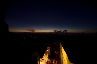 Svítání z vrcholu Sri Pady. Dole svítí ubytovny hlídačů a správců chrámu.