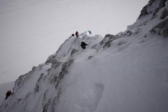 Pohled na sestupující skupinku. Zledovatělý sníh zahlazuje jinak rozervanou skálu.