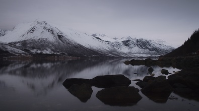 Calm coastline and dark mountains.
